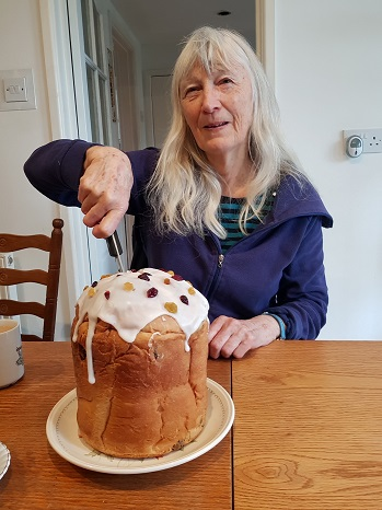 Clare cuts cake. Cake is a Кулич kindly baked by Larisa Seward — in Exeter, Devon